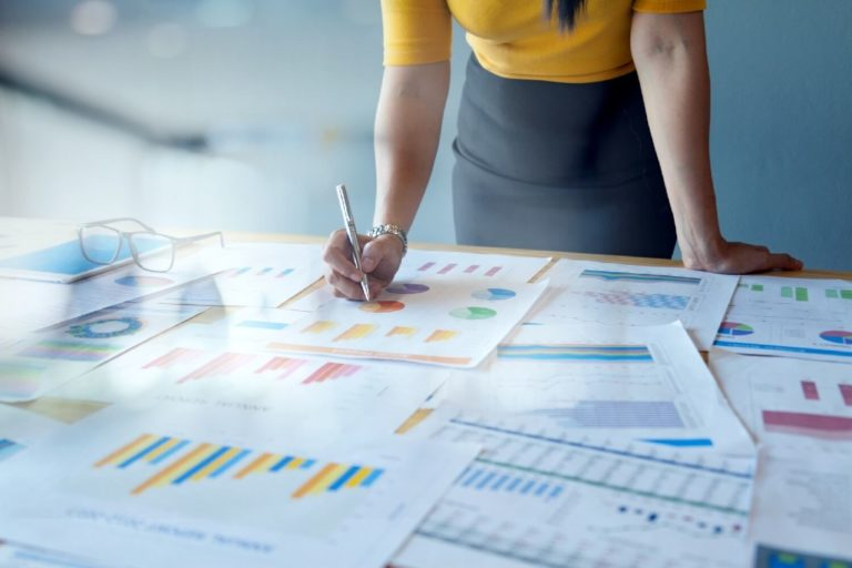 imagem de uma mulher analisando dados de pesquisas qualitativas e quantitativas
